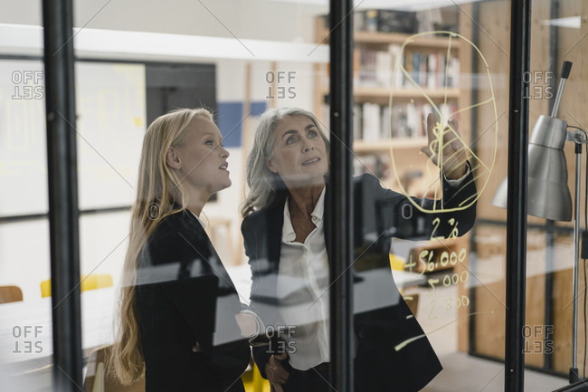 Mature and young businesswoman looking at chart on glass pane in office