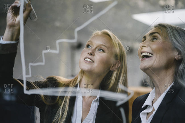 Happy mature and young businesswoman drawing chart on glass pane in office