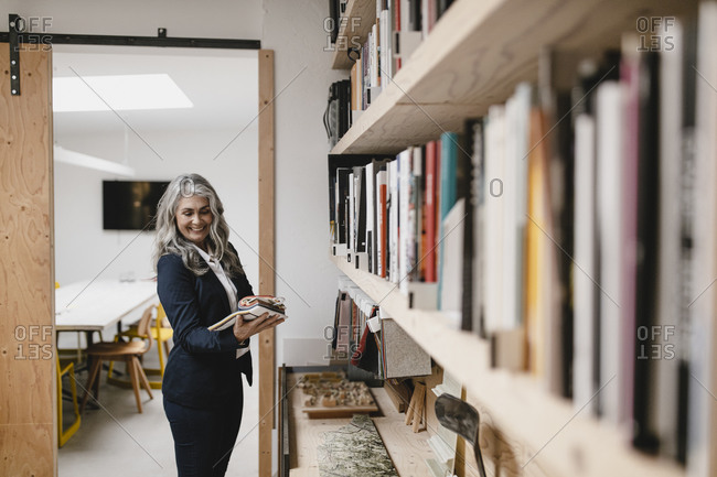 Smiling grey-haired businesswoman holding color samples in a loft office