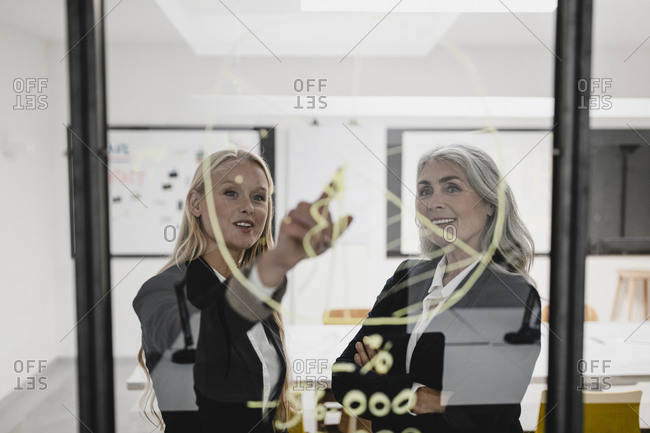 Mature and young businesswoman discussing chart on glass pane in office
