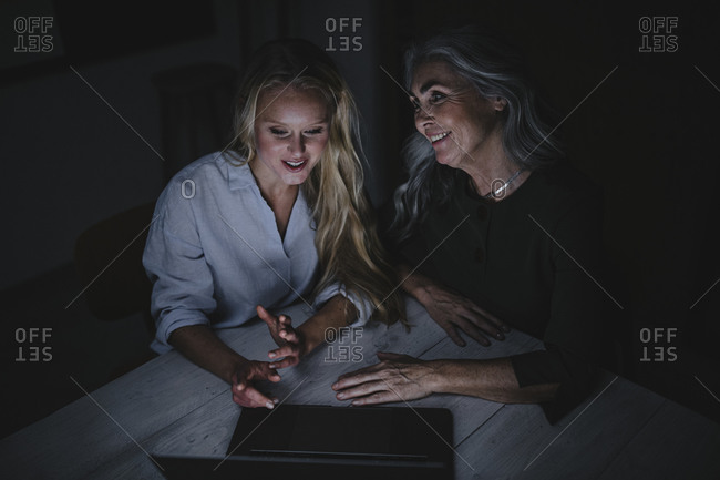 Mother and adult daughter looking at laptop on table in the dark