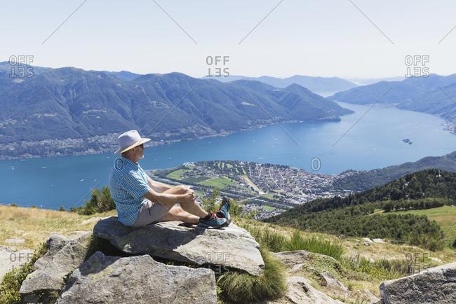 Hiker at Cimetta mountain top looking towards Lago Maggiore and Ascona- Locarno- Ticino- Switzerland