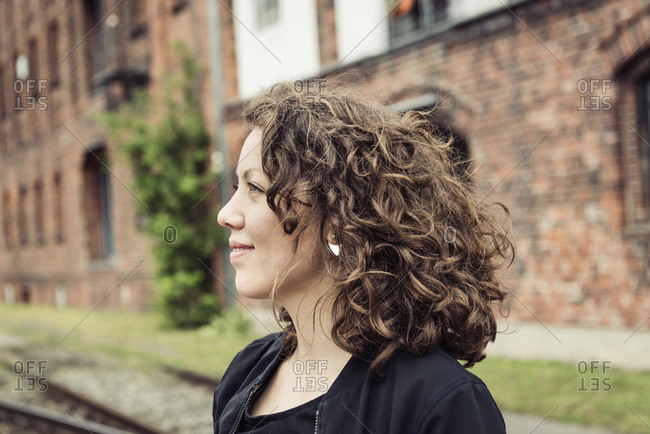 Smiling brunette woman with curly hair in front of a brick building and old rail tracks