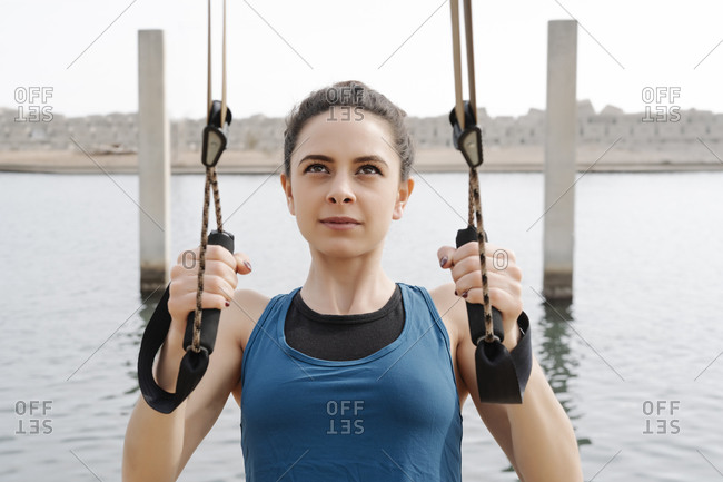 Young woman training on ropes at harbor