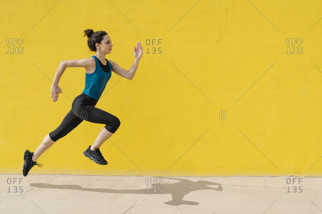 Young woman jogging in front of a yellow wall
