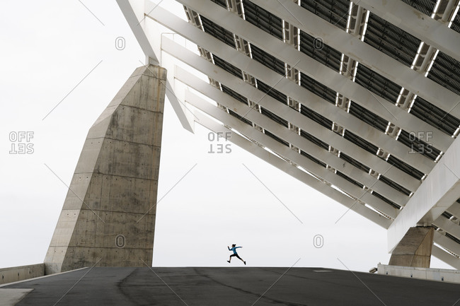 Young woman jogging at a modern building