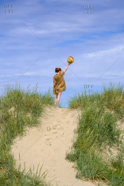 Teenage girl with hat standing in dunes at the beach- Farhult- Skane- Sweden