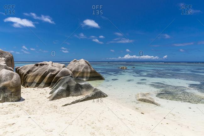 Seychelles- Boulders on sandy coastal beach of La Digue island in summer