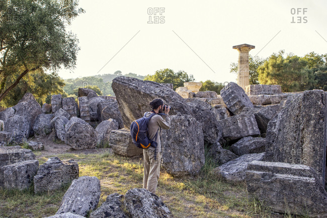 Greece- Olympia- Male tourist photographing ruins of ancient Temple of Zeus at sunset