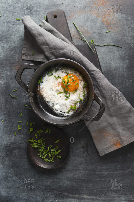 Fried egg with chives in cast iron pan