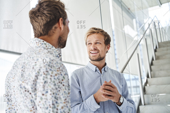 Two young businessmen talking at staircase