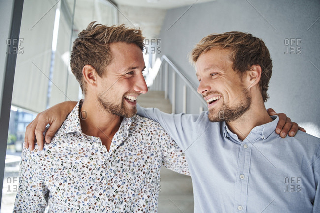 Portrait of two happy young businessmen embracing