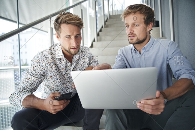 Two young businessmen sitting on stairs using laptop