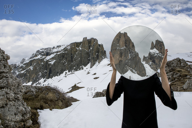 Woman covering head with mirror- reflecting Sella group in winter- Dolomites- Alto Adige- Italy
