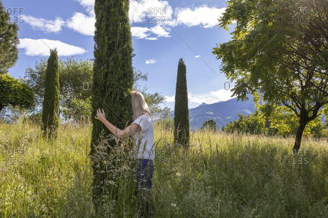 Woman standing in meadow- hugging cypresse