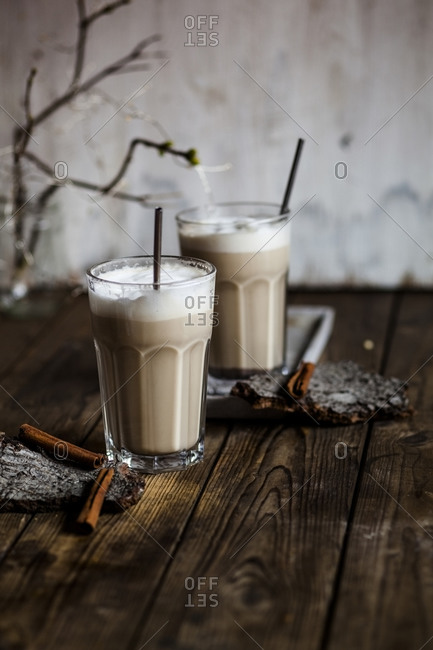 Glasses of iced chai with frothy milk and cinnamon
