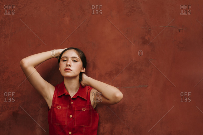 Portrait of female teenager wearing red strap dress in front of a wall