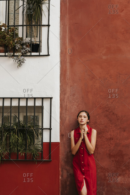 Female teenager wearing red strap dress leaning on a wall
