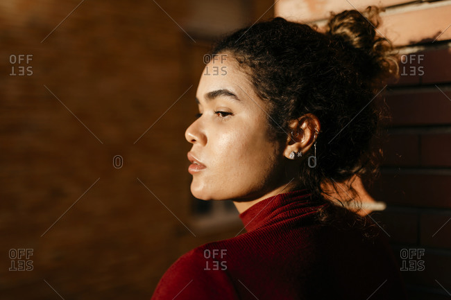 Portrait of young woman wearing red turtleneck pullover- sunlight on her face