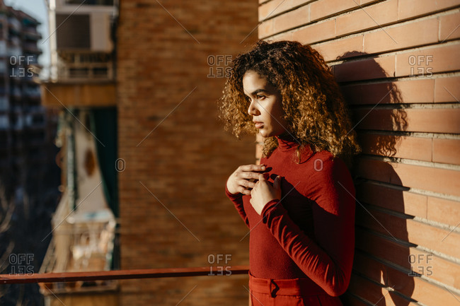 Portrait of young woman wearing red turtleneck pullover and standing on a balcony