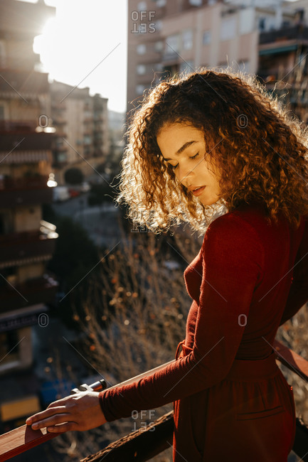Portrait of young woman wearing red turtleneck pullover- standing on balcony