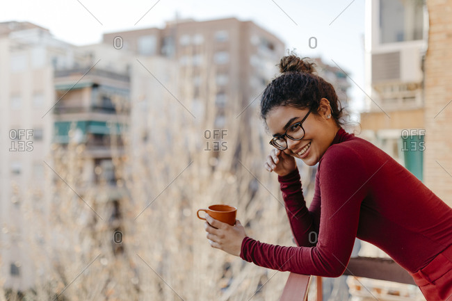 Portrait of young woman wearing red turtleneck pullover- hand on glasses- standing with a cup on a balcony