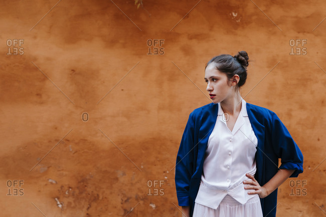 Portrait of female teenager wearing blue jacket and white clothes in front of a brown wall- hand on hip