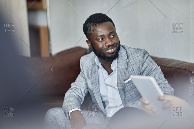 Portrait of a smiling businessman sitting on couch looking at colleague