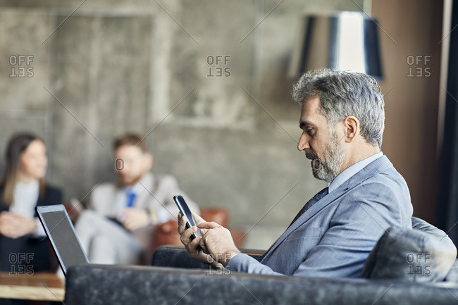 Businessman using laptop and smartphone in hotel lobby