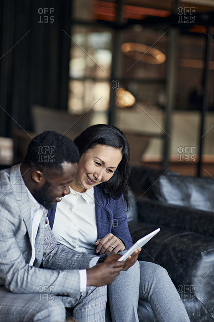 Businessman and businesswoman sitting on couch in hotel lobby sharing tablet