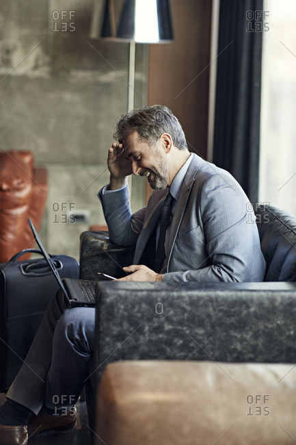 Smiling businessman using laptop and smartphone in hotel lobby