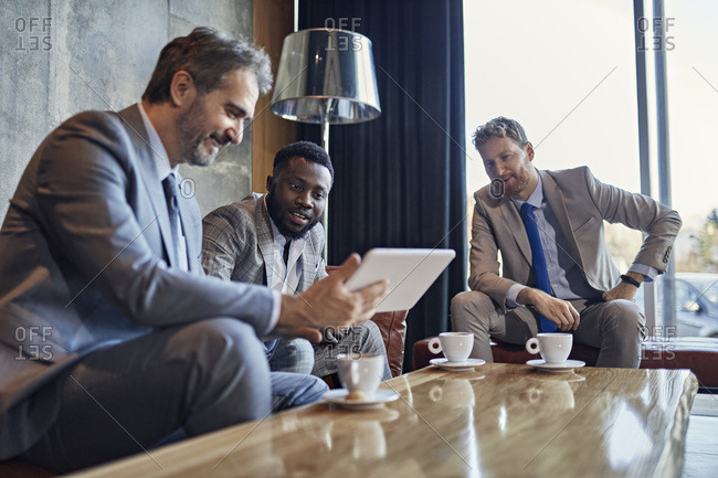 Three businessmen sitting in hotel lobby with tablet