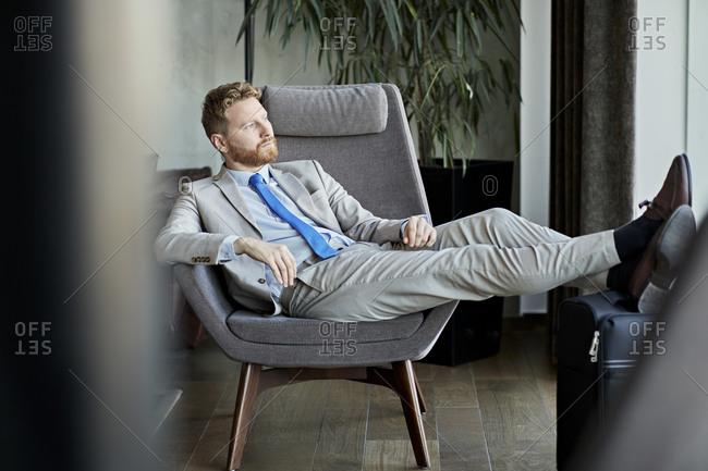 Businessman relaxing in hotel lobby