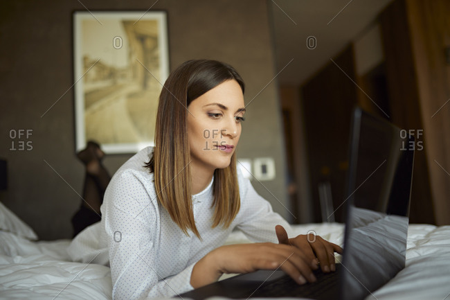 Businesswoman lying on bed in hotel room using laptop