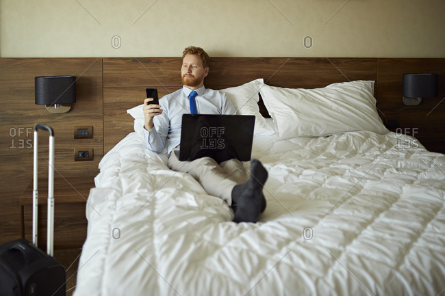 Businessman lying on bed in hotel room using laptop and cell phone