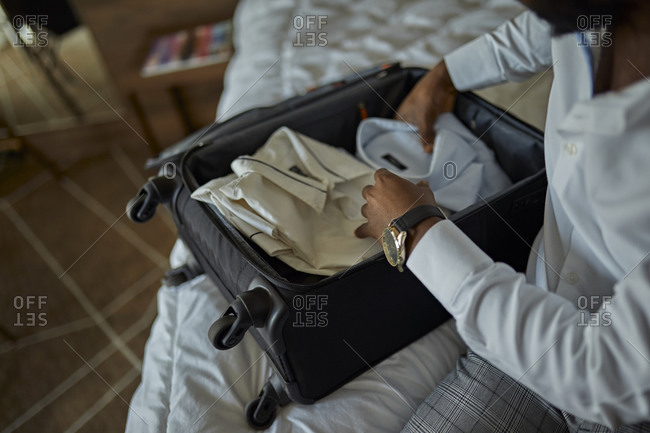 Businessman sitting on bed in hotel room packing his suitcase