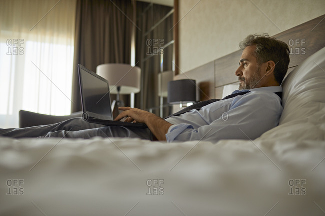 Businessman lying on bed in hotel room using laptop