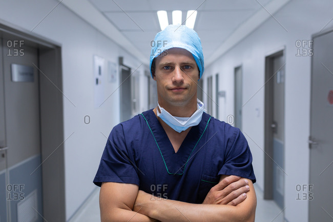 Portrait of handsome young Caucasian male surgeon standing with arms crossed in the corridor at hospital. Man is wearing surgical mask, gown and cap.