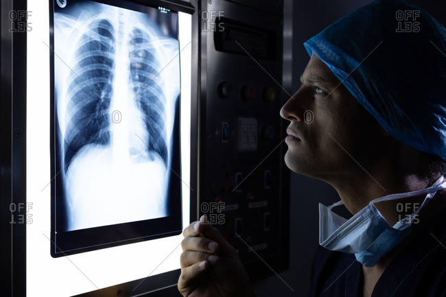 Side view of handsome young Caucasian male surgeon examining x-ray on light box in operation theater at hospital.