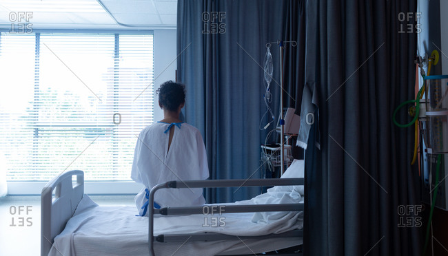 Rear view of thoughtful mixed-race female patient in hospital gown sitting on the bed while looking outside in hospital