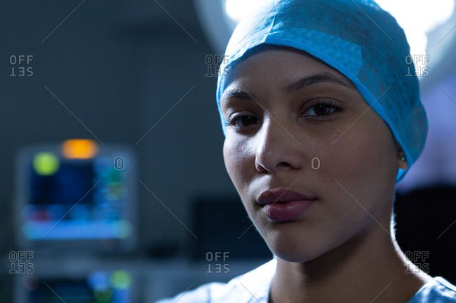 Portrait of young pretty mixed-race female surgeon standing while looking at camera in operation room of hospital. Surgeon is wearing surgical cap and gown. Shot in real medical hospital with doctors nurses and surgeons in authentic setting