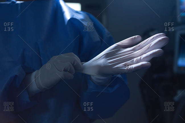 Mid section of mixed-race female surgeon with surgical gloves in operation room in hospital. Shot in real medical hospital with doctors nurses and surgeons in authentic setting