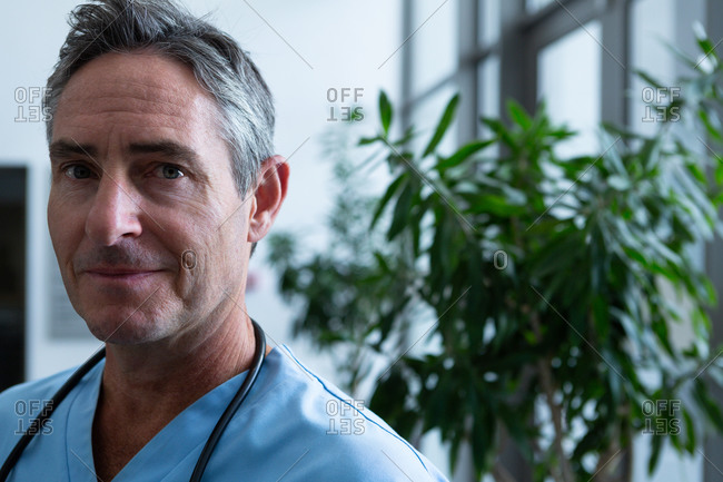 Portrait of handsome mature Caucasian male doctor looking at camera in corridor in hospital. Shot in real medical hospital with doctors nurses and surgeons in authentic setting