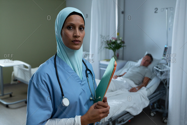 Portrait of beautiful mixed race female in hijab doctor standing with medical report while Caucasian male patient sleeps in the background in the hospital. Shot in real medical hospital with doctors nurses and surgeons in authentic setting