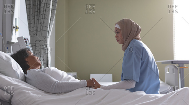 Side view of beautiful mixed-race female doctor consoling mixed-race female patient in the ward. Mixed-race female patient is lying in bed at the ward.