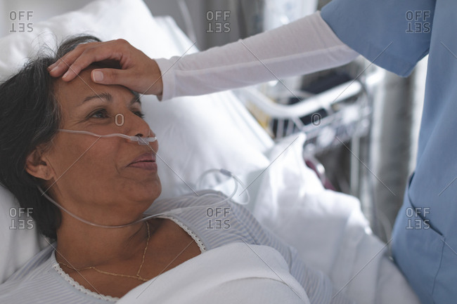 Close-up of mixed race female nurse checking the temperature of mixed-race female patient by hand in the ward at hospital