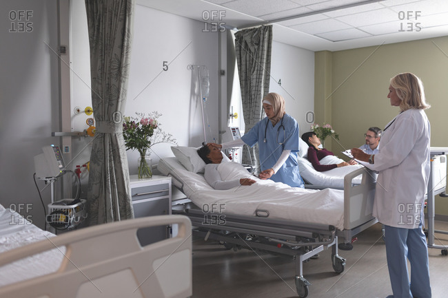 Front view of diverse female doctors interacting with mixed-race patient in the ward at hospital. In the background Caucasian man is holding the hand of Asian woman who is lying in bed at hospital.