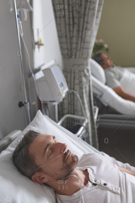 Side view of Caucasian male patient sleeping in bed in the ward at hospital. In the background senior mixed-race male patient lying in bed.