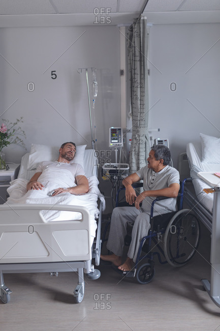 Side view of diverse male patients interacting with each other in the ward at hospital. Caucasian male patient lying in bed while mixed-race patient sits in wheelchair.