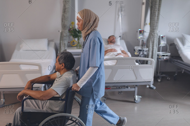 Side view of mixed-race female doctor in hijab pushing senior mixed-race male patient in wheelchair at hospital.